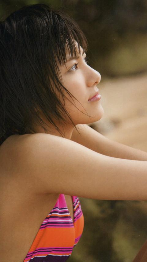 オレンジとパープルの水着でどこかを見つめる宮澤佐江さん。横顔がとってもきれいですね。