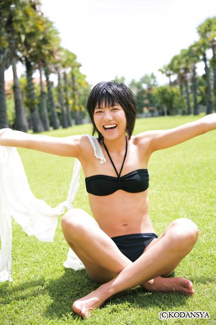 ブラックの水着で原っぱであぐらをかく宮澤佐江さん。開放的で気持ちよさそうですね。