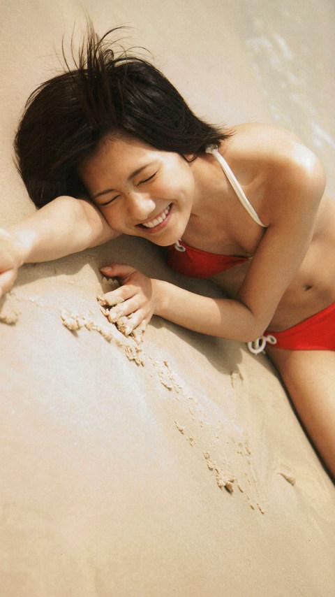 レッドの水着で砂浜に寝そべる宮澤佐江さん。キャッとした表情がとっても海を楽しんでいる様子が伝わってきます。