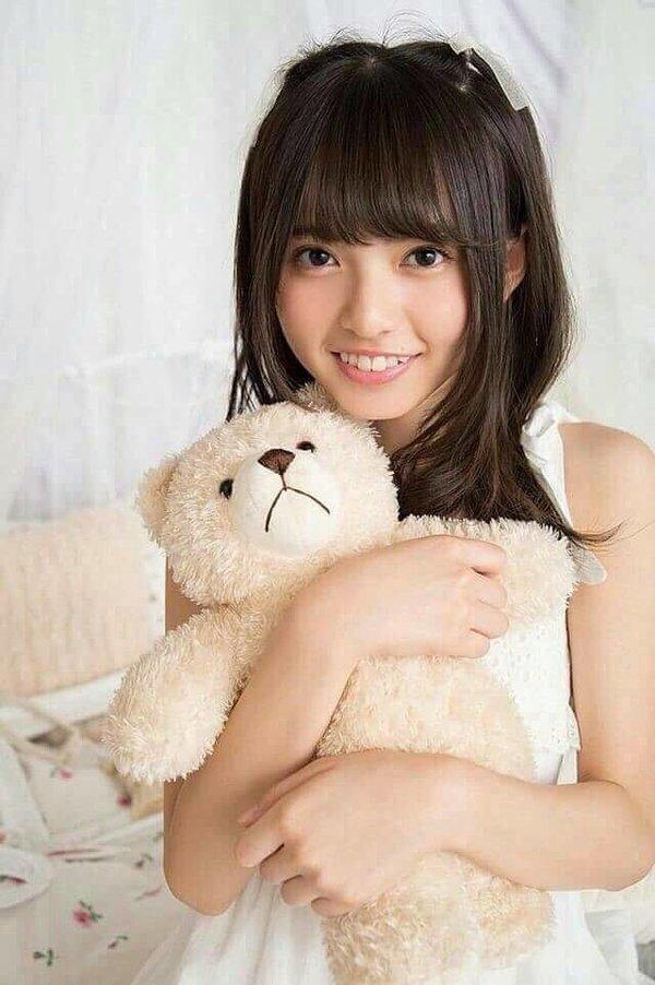 ホワイトのトップスでクマのぬいぐるみを抱っこする齋藤飛鳥さん。笑顔が珍しいですね。