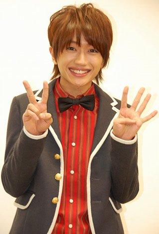 可愛らしいジャケット姿の西島隆弘さん。両手で「2」「4」を作って「にっしー」を表現しています。