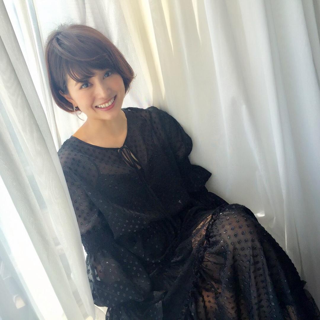 カーテンにもたれかかり笑顔の佐津川愛美さん。「キレイ」と「カワイイ」の両方を持ち合わせています。