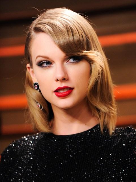 ブラックのスパンコールが華やかなトップスのテイラー・スウィフト。前髪から横髪にかけてのカールが美しいですね。