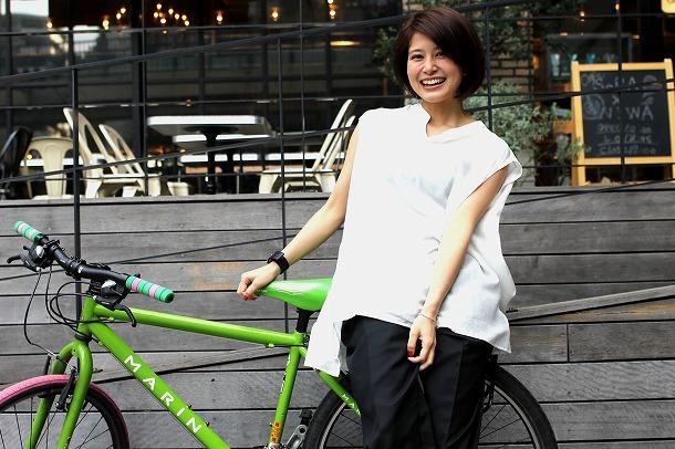 ホワイトのシャツでライムグリーンのシティバイクに乗る佐津川愛美さん。ナチュラルな笑顔に癒されます。