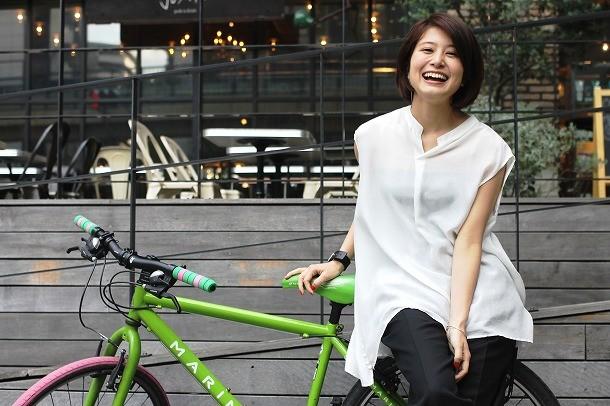 ホワイトのシャツでライムグリーンのシティバイクに乗る佐津川愛美さん。人の目を気にしてしまうタイプらしいです。
