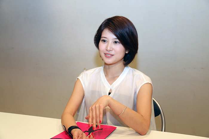 ホワイトのブラウス姿インタビューに答える佐津川愛美さん。黒目がちな瞳が魅力的ですね。