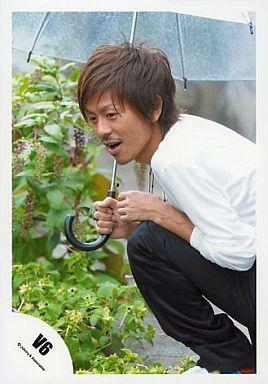 傘をさしてしゃがみ込む森田剛さん。何かを発見したような表情をしています。